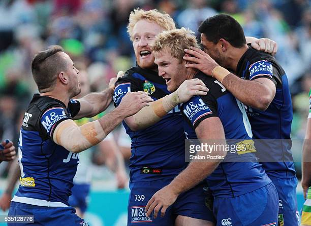 Aiden Tolman of the Bulldogs is congratulated by team mates after scoring a try during the round 12 NRL match between the Canberra Raiders and the...