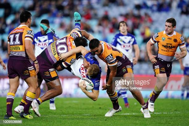 Aiden Tolman of the Bulldogs is tackled during the round 21 NRL match between the Canterbury Bulldogs and the Brisbane Broncos at ANZ Stadium on...