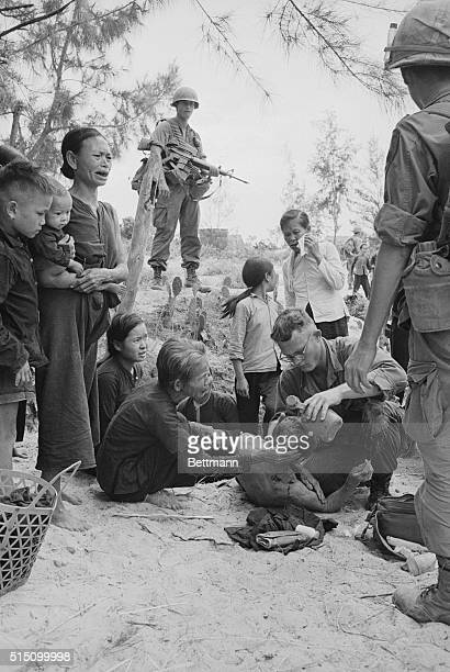 Aids Wounded Da Nang S Vietnam Trooper of US 1st Cavalry stands guard as he and villagers watch medic treat wounded Vietnamese following brief...