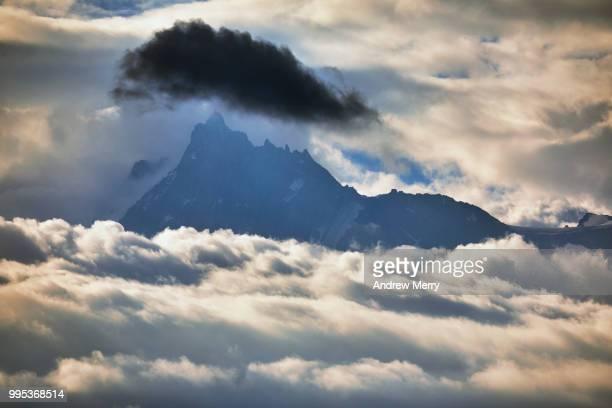 aiguille du midi summit, peak, mountain range appearing above the clouds with large dark cloud - pinnacle peak stock-fotos und bilder