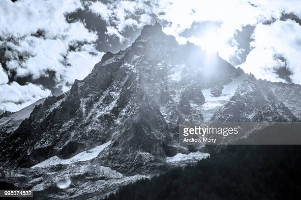aiguille du midi summit, peak, mountain range back lit by sun and clouds - pinnacle peak stock pictures, royalty-free photos & images