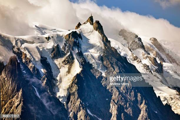 aiguille du midi summit, peak, mountain range with clouds and blue sky - aiguille de midi stock photos and pictures