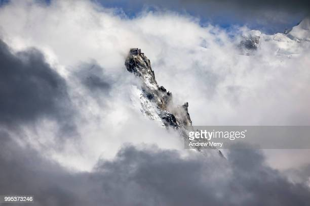 aiguille du midi summit, peak partially obscured by dramatic clouds - pinnacle stock pictures, royalty-free photos & images