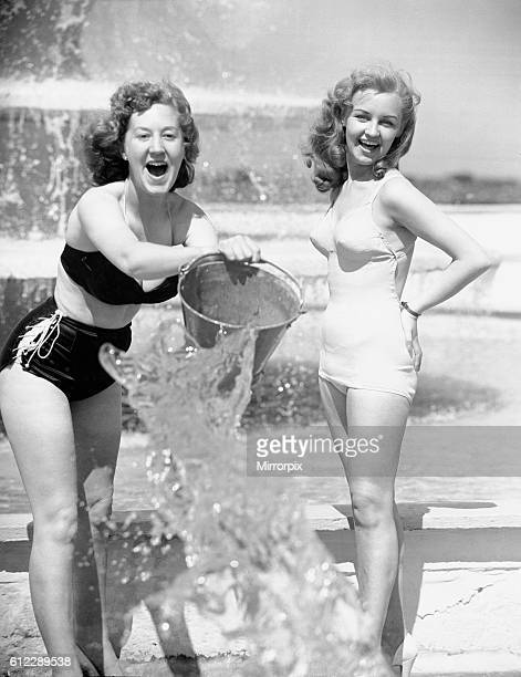 Aileen Kearney and her friend Marjorie Greenhalgh throwing a bucket of water over photographer Cyril Maitland during the weekend heat wave at Butlins...
