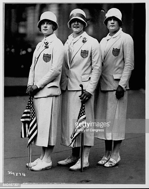 Aileen Riggin Gertrude Ederle and Helen Wainright stand in their Olympic team uniforms and hold American flags after returning from the 1920 Olympics...