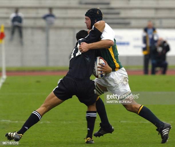 L'ailier néozélandais Hosea Gear est plaqué par le troisième ligne centre sudafricain Paul Delport le 20 avril 2003 à Bondoufle lors de la finale de...