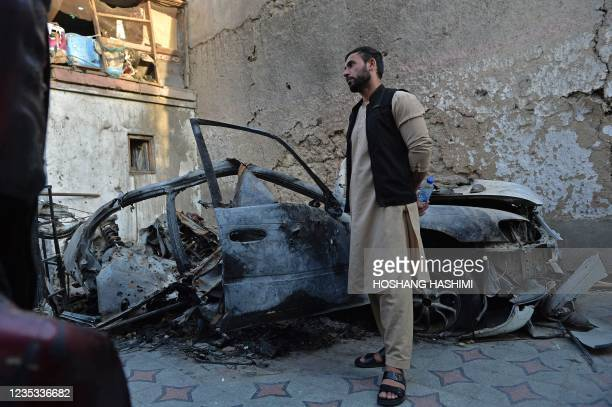 Aimal, brother of Ezmarai Ahmadi, stands next to the wreckage of a vehicle that was damaged in a US drone strike in the Kwaja Burga neighbourhood of...