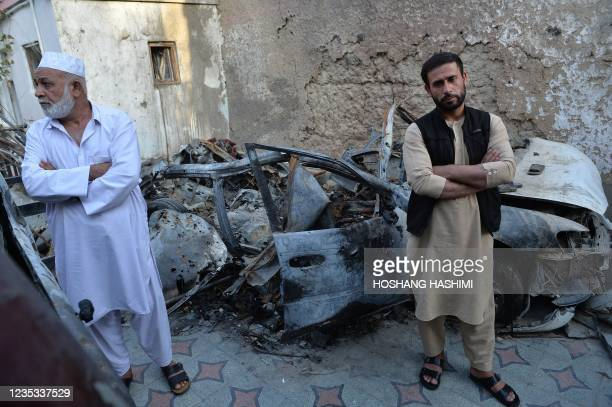Aimal , brother of Ezmarai Ahmadi, stands next to the wreckage of a vehicle that was damaged in a US drone strike in the Kwaja Burga neighbourhood of...