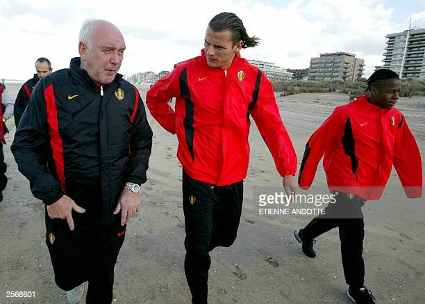 Aime Anthuenis and players Daniel Van Buyten and Emile Mpenza walk 07 October 2003 on the beach of De Panne during a training session of Belgium's...