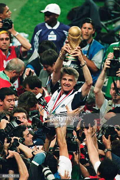 Aime Jacquet coach of the French national team holds up the 1998 FIFA World Cup trophy as his team carries him on their shoulders after their victory...
