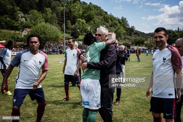 Aime Jacquet former coach of French national football team hugs a player on the pitch before a football match between former French Team members and...