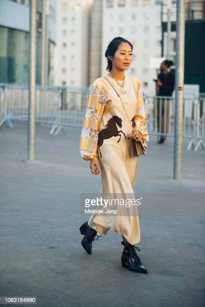 Aimee Song exits the Chloe show in a yellow dress with horses tan bag and black boots during Paris Fashion Week Spring/Summer 2019 on September 27...