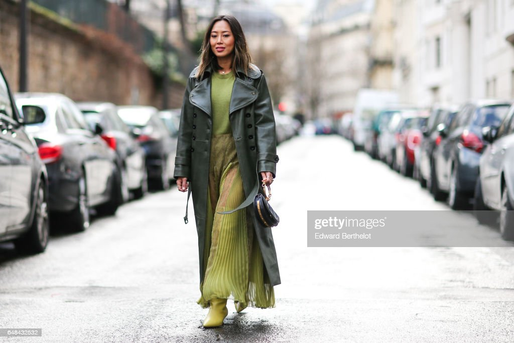 Aimee Song, fashion blogger from Song of Style, wears a green leather coat, a green pleated dress, and green shoes, outside the Valentino show, during Paris Fashion Week Womenswear Fall/Winter 2017/2018, on March 5, 2017 in Paris, France.