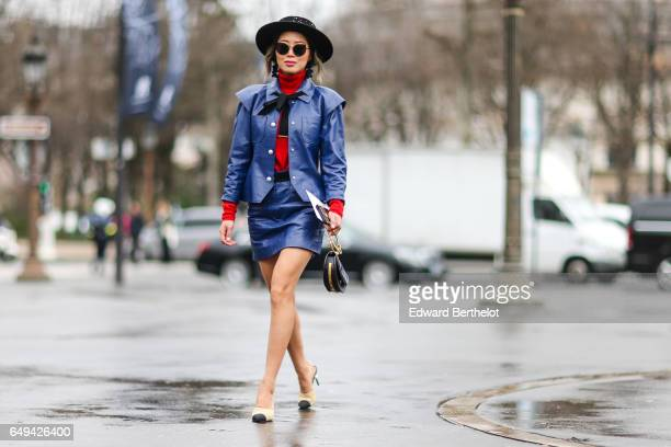 Aimee Song fashion blogger from Song of Style wears a hat a blue jacket a blue skirt a red top outside the Chanel show during Paris Fashion Week...