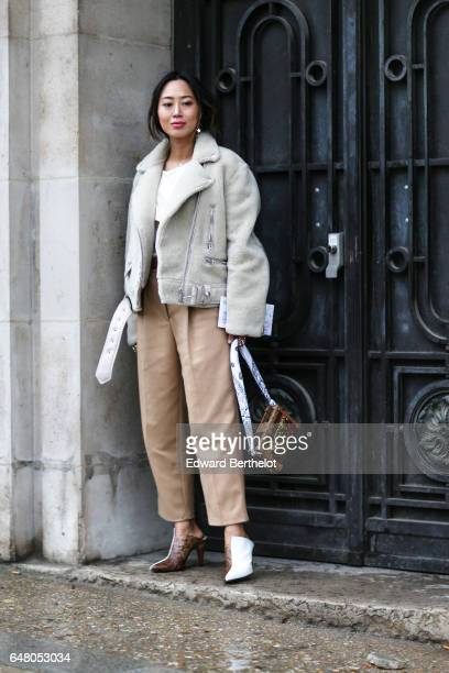 Aimee Song fashion blogger from Song of Style wears a white fur aviator jacket a white top beige pants bicolor white and snake print shoes and a...