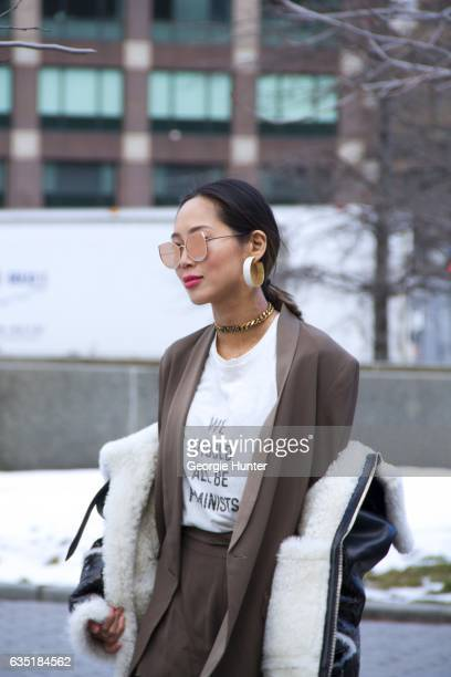 Aimee Song is seen at Spring Studios outside the Phillip Lim show wearing white feminist protest tshirt black leather and shearling jacket cat eye...