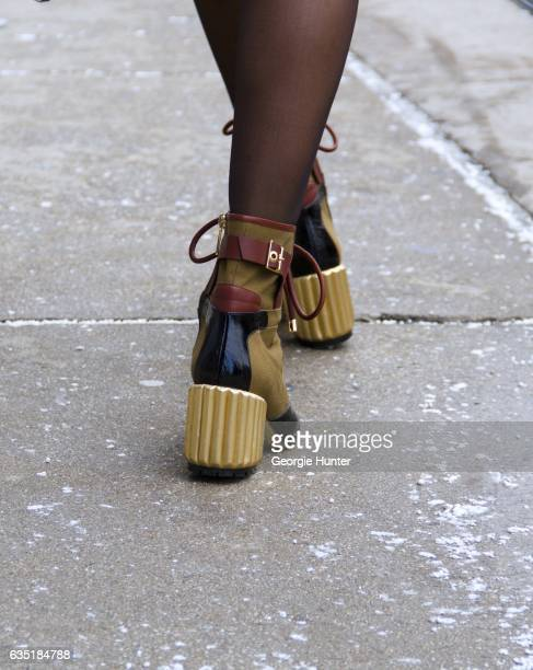 Aimee Song is seen at Spring Studios outside the Phillip Lim show wearing gold black and tan laceup ankle booties with gold metal block heel on...