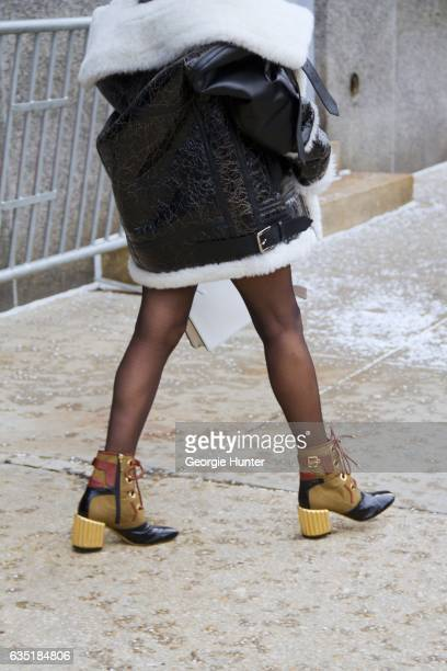 Aimee Song is seen at Spring Studios outside the Phillip Lim show wearing cracked black leather and shearling jacket and gold black and tan laceup...