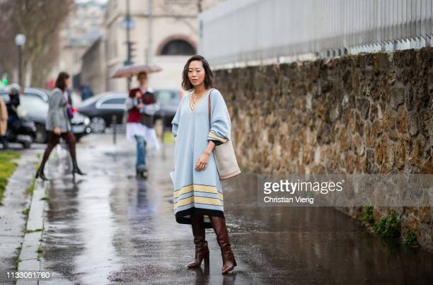 Aimee Song is seen blue v neck dress boots bag outside Loewe during Paris Fashion Week Womenswear Fall/Winter 2019/2020 on March 01 2019 in Paris...