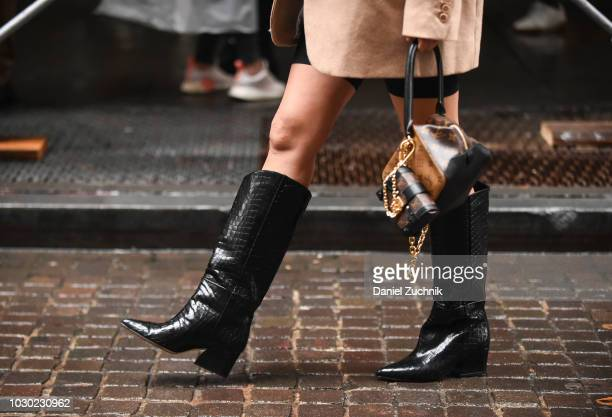 Aimee Song is seen wearing a beige coat black leather boots and a Louis Vuitton bag outside the Tibi show during New York Fashion Week Women's S/S...
