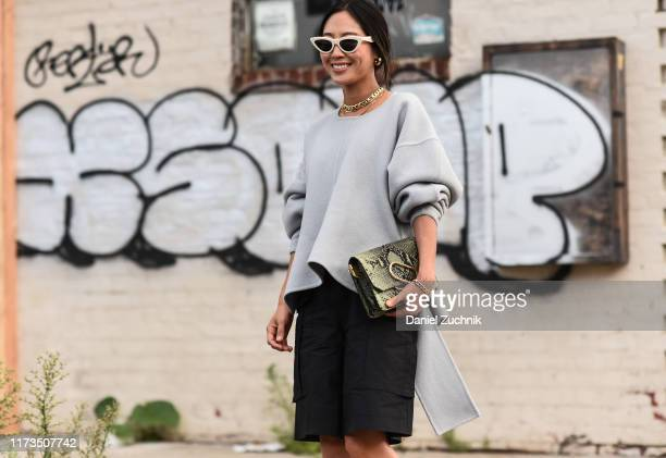 Aimee Song is seen wearing a gray Phillip Lim sweater, black skirt and white sunglasses outside the Phillip Lim show during New York Fashion Week...