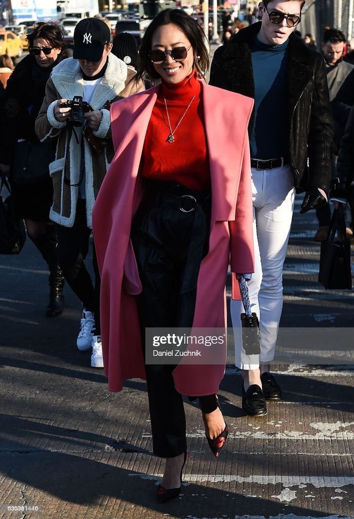 Aimee Song is seen wearing a pink coat, red sweater and black leather pants outside the Coach show during New York Fashion Week: Women's Fall/Winter 2017 on February 14, 2017 in New York City.