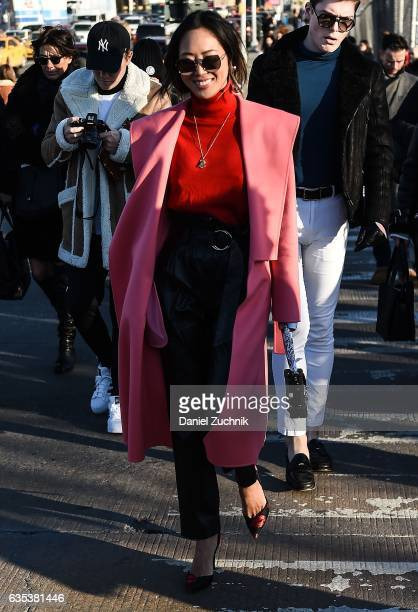 Aimee Song is seen wearing a pink coat red sweater and black leather pants outside the Coach show during New York Fashion Week Women's Fall/Winter...