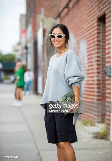 Aimee Song is seen wearing grey jumper, black shorts, green bag with snake print outside 3.1 Phillip Lim during New York Fashion Week September 2019...