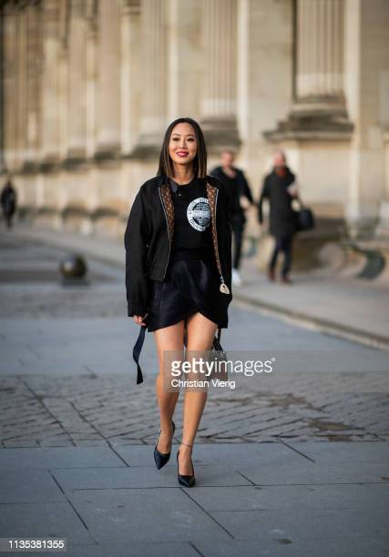 Aimee Song is seen wearing jacket mini skirt bag heels with printed label outside Louis Vuitton during Paris Fashion Week Womenswear Fall/Winter...
