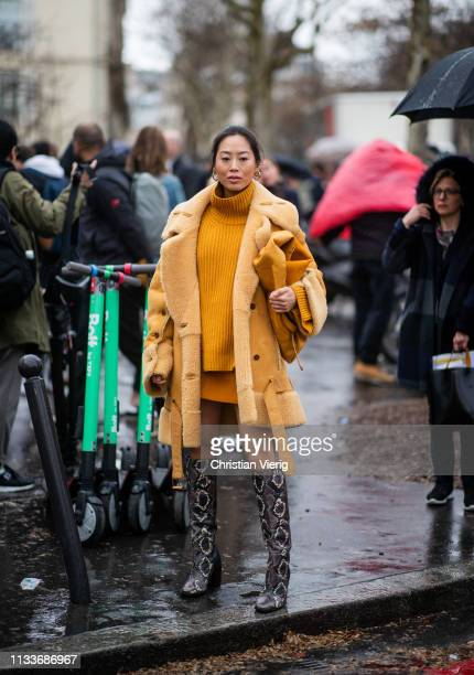 Aimee Song is seen wearing mustard shearling coat turtleneck boots with snake print outside Sacai during Paris Fashion Week Womenswear Fall/Winter...