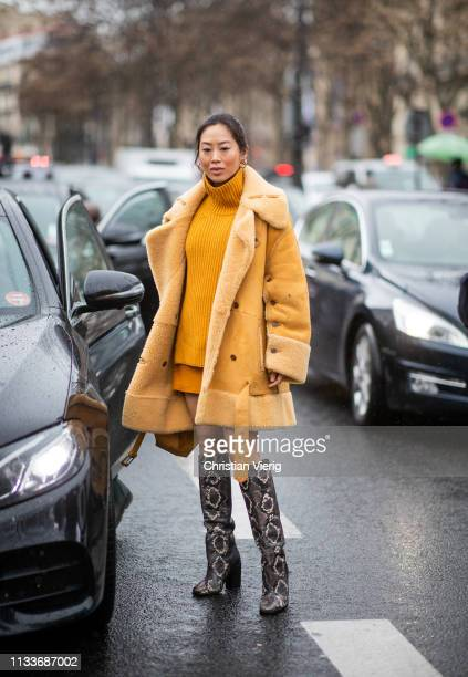 Aimee Song is seen wearing mustard shearling coat, turtleneck, boots with snake print outside Sacai during Paris Fashion Week Womenswear Fall/Winter...