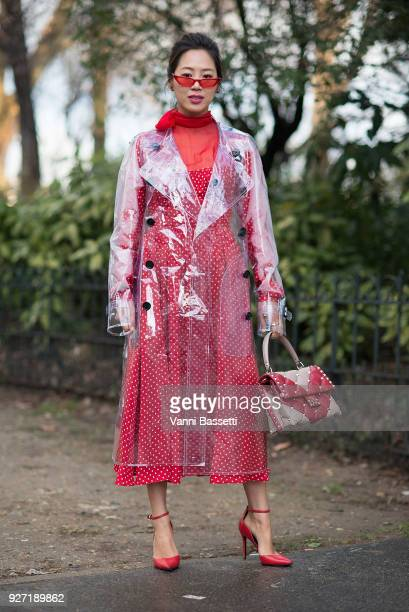 Aimee Song poses wearing a Burberry trench coat and Valentino dress and bag after the Valentino show at Les Invalides during Paris Fashion Week...