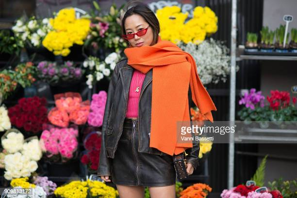 Aimee Song poses wearing a leather jacket Acne Studios scarf and Louis Vuitton bag after the Acne Studios show during Paris Fashion Week Haute...