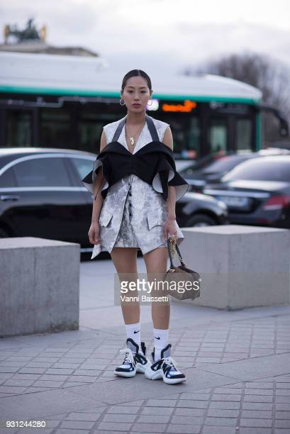 Aimee Song poses wearing Louis Vuitton before the Louis Vuitton show at the Pyramide du Louvre during Paris Fashion Week Womenswear FW 18/19 on March...