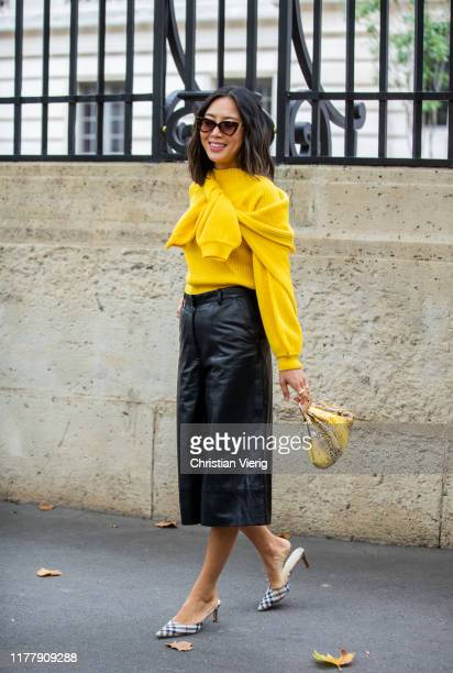 Aimee Song seen wearing yellow knit, black leather shorts, bags with snake print outside Altuzarra during Paris Fashion Week Womenswear Spring Summer...