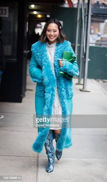 Aimee Song walks outside of the Tibi show wearing a suede trench coat during New York Fashion Week on February 10, 2019 in New York City.