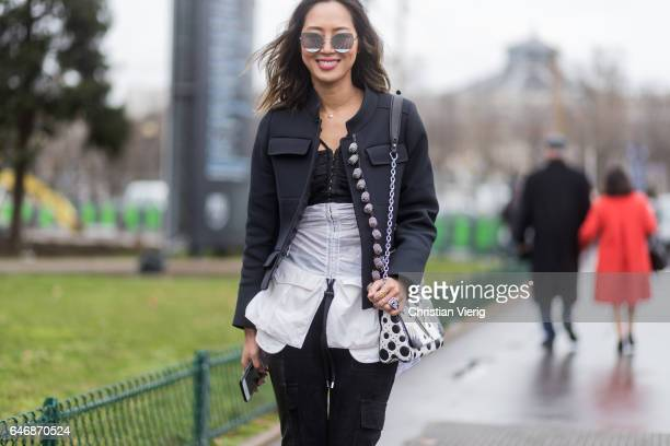 Aimee Song wearing a black jacket corset black pants white Louis Vuitton bag outside Maison Margiela on March 1 2017 in Paris France