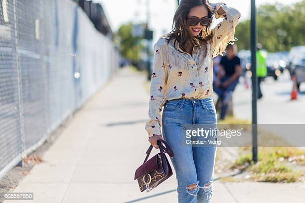 Aimee Song wearing a Chloe bag denim jeans and a blouse with fringes outside Coach on September 13 2016 in New York City