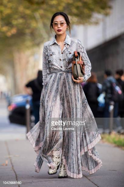 Aimee Song wearing a maxi snake print dress snake print boots and Loewe bag is seen before the Loewe show on September 28 2018 in Paris France