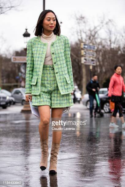 Aimee Song wearing a nude turtleneck top green jacket with matching shorts and nude and black boots is seen outside Chanel on Day 9 Paris Fashion...