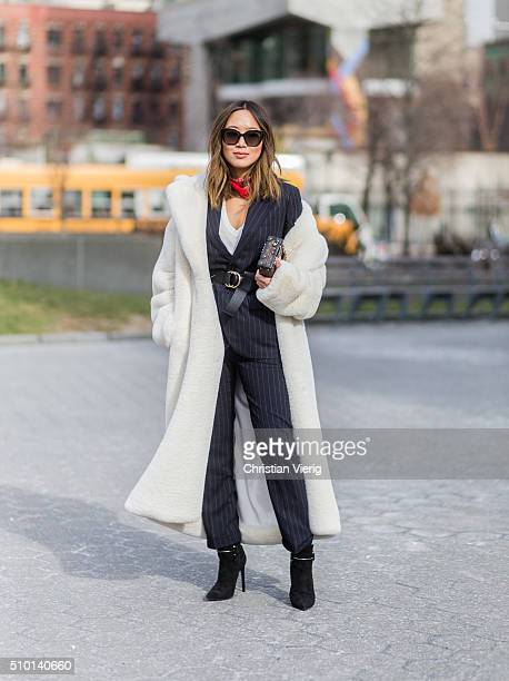 Aimee Song wearing a Polo Ralph Lauren dark blue pinstripe suit and a white fake fur coat and a Louis Vuitton clutch seen outside Jason Wu during New...