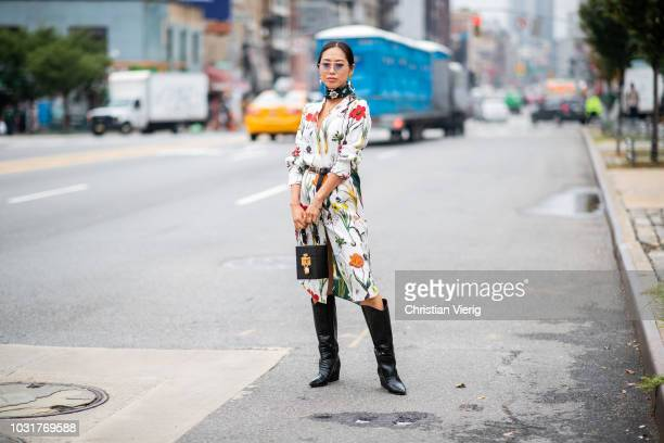 Aimee Song wearing black boots dress with floral prints seen outside Oscar de la Renta during New York Fashion Week Spring/Summer 2019 on September...