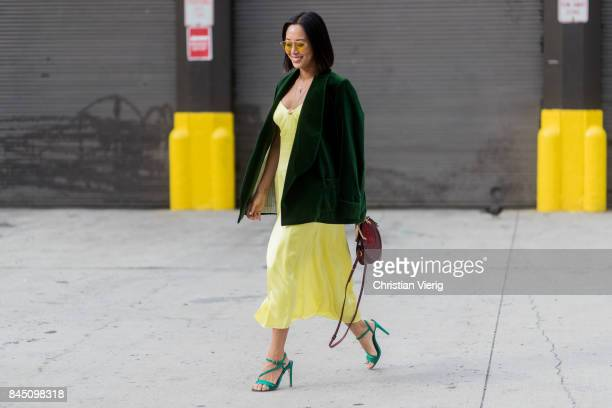 Aimee Song wearing green velvet jacket yellow dress seen in the streets of Manhattan outside Jonathan Simkhai during New York Fashion Week on...