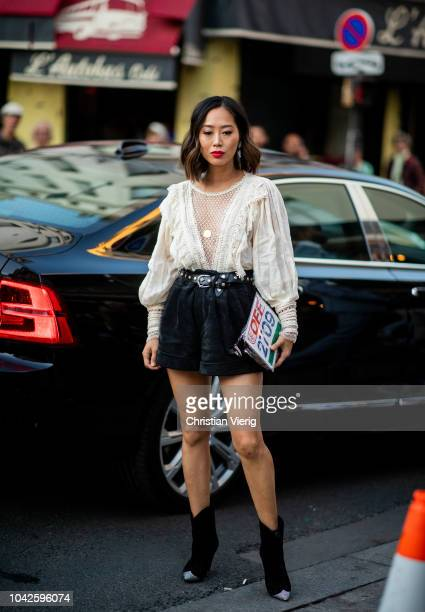 Aimee Song wearing white ruffled blouse black shorts is seen outside Off White during Paris Fashion Week Womenswear Spring/Summer 2019 on September...