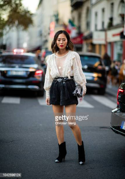 Aimee Song wearing white ruffled blouse, black shorts is seen outside Off White during Paris Fashion Week Womenswear Spring/Summer 2019 on September...
