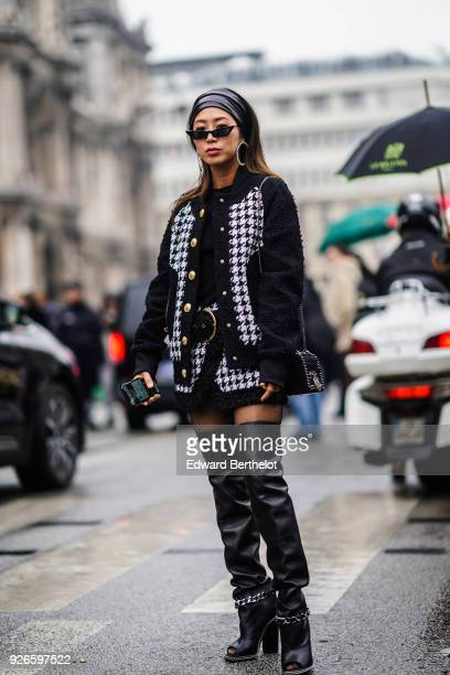 Aimee Song wears a black and white tweed jacket black thigh high leather boots sunglasses a bandanna over the hair outside Balmain during Paris...