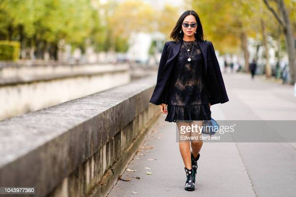 Aimee Song wears a black blazer jacket a black lace dress a blue bag outside Valentino during Paris Fashion Week Womenswear Spring/Summer 2019 on...
