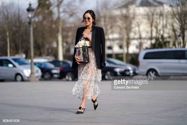 Aimee Song wears a black blazer jacket a lace dress a bag with flowers sunglasses outside Chanel during Paris Fashion Week Womenswear Fall/Winter...