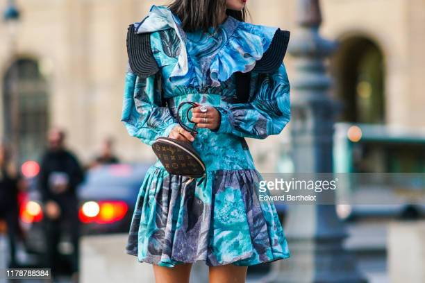 Aimee Song wears a blue and turquoise ruffle dress with floral print and attached corset earrings a Vuitton Toupie bag outside Louis Vuitton during...