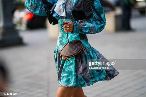 Aimee Song wears a blue and turquoise ruffle dress with floral print and attached corset, earrings, a Vuitton Toupie bag, white shoes, outside Louis...